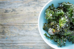 Kale chips with salt in pastel blue bowl from above Stock Images