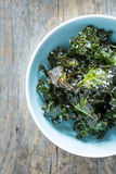 Kale chips with salt in pastel blue bowl captured from above (top view) Royalty Free Stock Photo