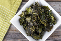 Kale chips snack. Healthy snack seasonned kale chips bowl on rustic wood table Stock Photos