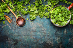 Kale in cooking pot with wooden spoon on  rustic background, top view, border. Stock Photo