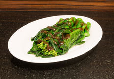 Kale fried in oyster sauce on stone table Royalty Free Stock Images