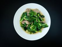 Kale fried with pork in oyster sauce menu on white plate for meal with black background. Thai food.  stock images