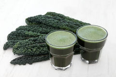 Kale Heath Drink. Kale health drink with fresh vegetable leaves over distressed white wood background. High in vitamins and antioxidants. Selective focus stock photos