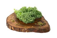Kale leafs and pumpkin seeds on wooden cutting board Royalty Free Stock Images
