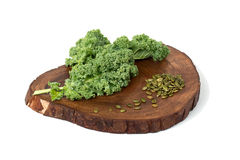 Kale leafs and pumpkin seeds on wooden cutting board Stock Photography
