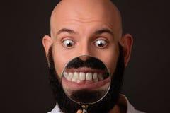 Kale mens die zijn tanden via vergrootglas op donkere achtergrond tonen Stock Fotografie