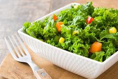 Kale salad in bowl with carrot, pepper and sweet corn. On wooden background Stock Image