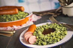 Kale with smoked sausage or 'Boerenkool met worst'. A rustic kitchen with a plate with 'Boerenkool met worst' or kale with smoked sausage, a traditional Dutch Royalty Free Stock Images