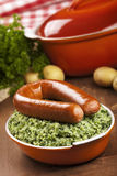 Kale with smoked sausage or 'Boerenkool met worst'. A rustic table with a dish with 'Boerenkool met worst' or kale with smoked sausage, a traditional Dutch meal Stock Images