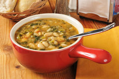 Kale and white bean soup. A bowl of healthy kale and white bean soup with dinner rolls Stock Images
