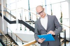 Kale Zakenman Writing On Clipboard tegen Stappen in Bureau stock foto