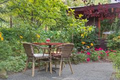 Table and chairs at patio garden restaurant in summer stock image