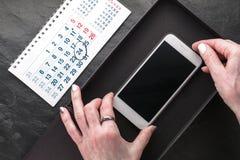 Kalendarz, czarny pudełko i telefon w ręka widoku od above, Obraz Royalty Free