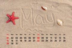 Kalendarz z rozgwiazdą i seashells na piasku wyrzucać na brzeg Maj 2016 Obraz Royalty Free