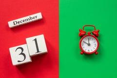 Kalender am 31. Dezember und roter Wecker stockfotografie