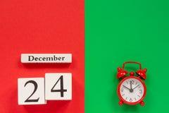 Kalender am 24. Dezember und roter Wecker lizenzfreie stockfotos