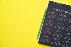 Kalender en potlood op de lijst met gele achtergrond Royalty-vrije Stock Foto's
