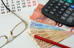 Kalender, exponeringsglas, röd blyertspenna, euro och räknemaskin Arkivbilder
