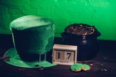 kalender, kakor i form av treklövern, grön irländsk hatt och kruka med guld- mynt på trä vektor illustrationer