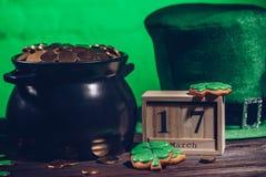 kalender, kakor i form av treklövern, grön irländsk hatt och kruka med guld- mynt, st-patricks royaltyfri fotografi