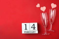 Kalender mit Datum vom 14. Februar, zwei Champagnerglas und rosa Herzen lizenzfreie stockfotos