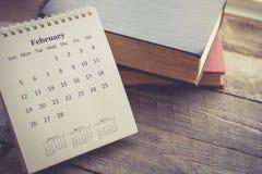 Kalender mit dem Buch auf hölzernem Hintergrund im Weinlese-Ton Lizenzfreies Stockfoto