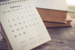 Kalender mit dem Buch auf hölzernem Hintergrund im Weinlese-Ton Lizenzfreie Stockfotos
