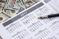Kalender mit einem Stift und Dollar Stockbilder