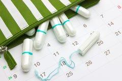 Kalender och sanitära mjuka bomullstamponger för menstruation Kritiska dagar för kvinna, gynekologisk menstruations- cirkulering  royaltyfri fotografi
