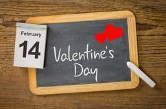 Kalender och svart tavla som visar Februari 14 Arkivfoton