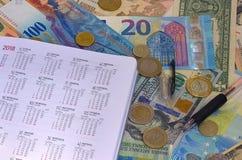 Kalender på bakgrund för euro- och dollarräkning-, räknemaskin-, bläckpenna- och myntpengar Arkivfoto