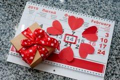 Kalender till valentindagen med röda pappers- hjärtor royaltyfri fotografi