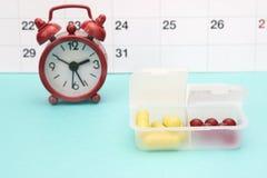 Kalender, Uhren und gelbe Pillen im Pillenkasten Pharmazeutisch, Tabletten und gelbe Kapseln, roter Wecker Medizinischer Begriffs Lizenzfreie Stockfotografie