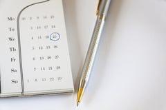 Kalender und Pen On White On White-Hintergrund Stockfotos