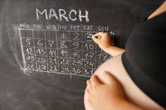 Kalender van de zwangere vrouw de tellende dagen van maandmaart met een kalender voor de geboorte van een kind op een bord Het co stock afbeelding