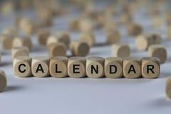 Kalender - Würfel mit Buchstaben, Zeichen mit hölzernen Würfeln Stockfotografie