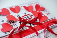 Kalender zum Valentinsgrußtag mit roten Papierherzen stockbild