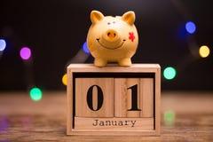 Kalenderdatum av finansieringsårstarten, 1st januari med spargrisen på mörk bakgrund royaltyfri bild