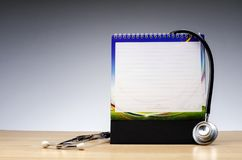 Kalendernotepad och stetoskop på träskrivbordet över lutningeffektbakgrund royaltyfria bilder