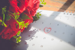 Kalenderseite mit einem rote Hand schriftlichen Herzhöhepunkt auf Februar Lizenzfreies Stockfoto