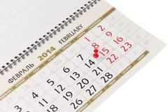 Kalenderseite mit roten Reißzwecken am 14. Februar 2014. Stockfoto