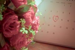 Kalendersida med en skriftlig hjärtaviktig för röd hand på Februar Arkivfoton