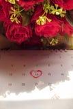 Kalendersida med en skriftlig hjärtaviktig för röd hand på Februar Fotografering för Bildbyråer