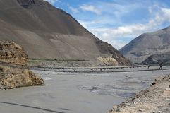 The Kali Gandaki River, with a suspension bridge across it, against the backdrop of the Himalayan mountains.  Trekking to the clos. Ed zone of Upper Mustang Stock Images