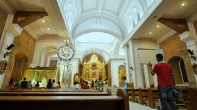 KALIBO, ФИЛИППИНЫ - 5-ОЕ ЯНВАРЯ 2018: Интерьер внутри католического виска в Филиппинах Прихожане и туристы сток-видео