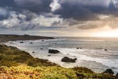 Kalifornien-Küste während des bewölkten Sonnenuntergangs Stockbilder