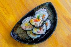 Kalifornien makirulle i den svarta maträtten på trätabellen Royaltyfri Bild
