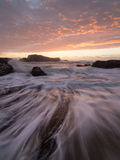 Kalifornien solnedgång med att rusa vågor Fotografering för Bildbyråer