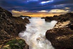 海挥动鞭子线在海滩的冲击岩石 库存照片