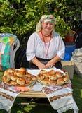 KALININGRAD, RÚSSIA - 15 DE AGOSTO DE 2014: A mulher alegre em vendas de um terno do nacional rola na feira da faculdade criadora Fotografia de Stock